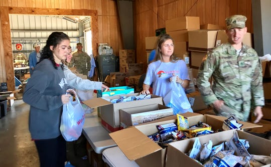 Hailey Ensor, left, and Alexis Workman, volunteers from Experience Church in Tallahassee, bag food for Hurricane Michael victims Sunday at the town hall in Grand Ridge.