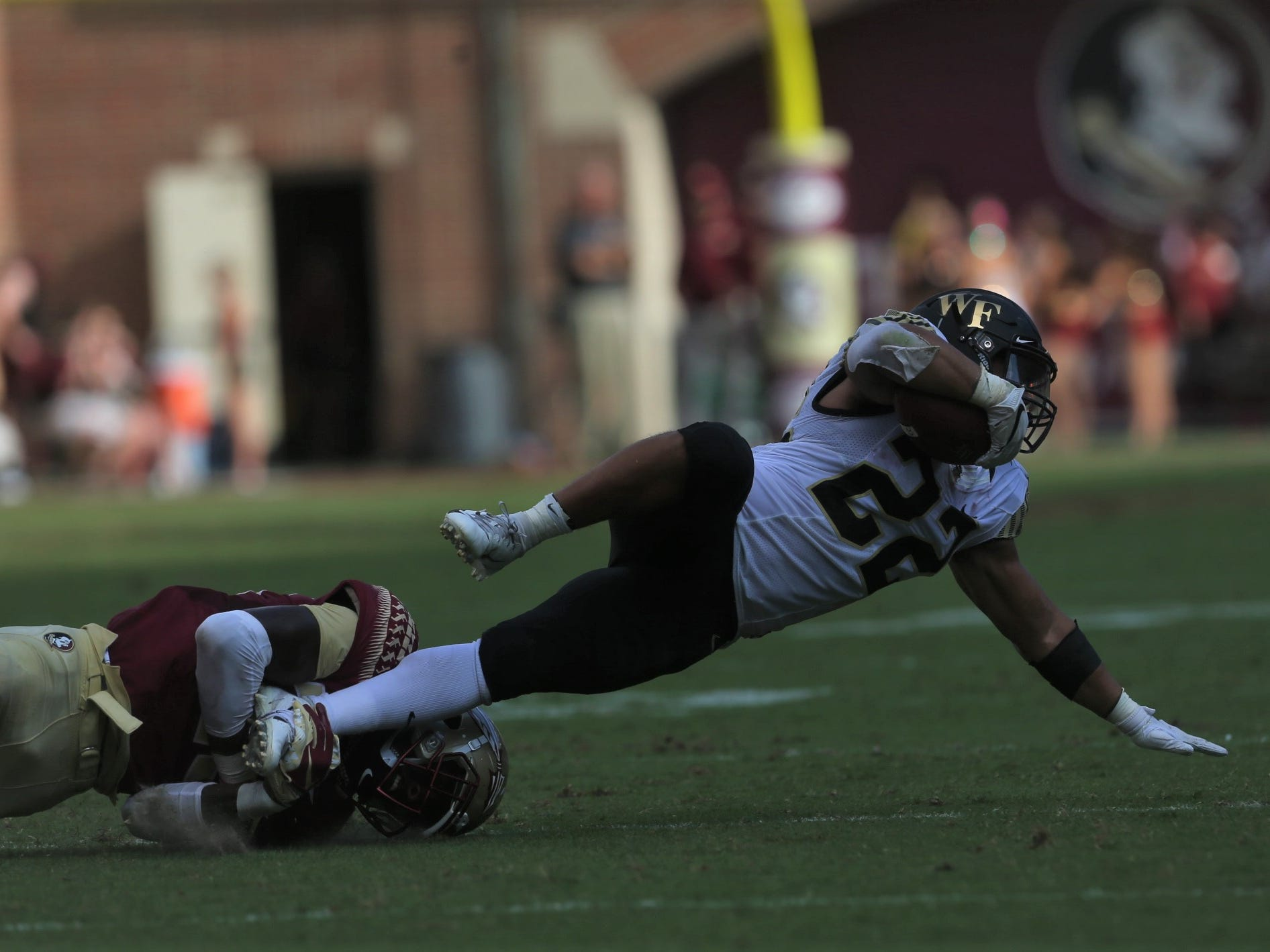 Wake Forest running back Matt Colburn II gets tackled by a Florida State defender during a game at Doak Campbell Stadium on Saturday, Oct. 20, 2018.