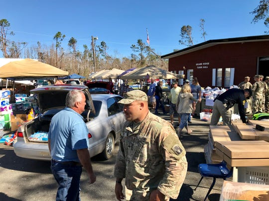 Grand Ridge City Manager J.R. Moneyham, left, walks through the parking lot of the town hall, now a point of distribution for food, water and other supplies.