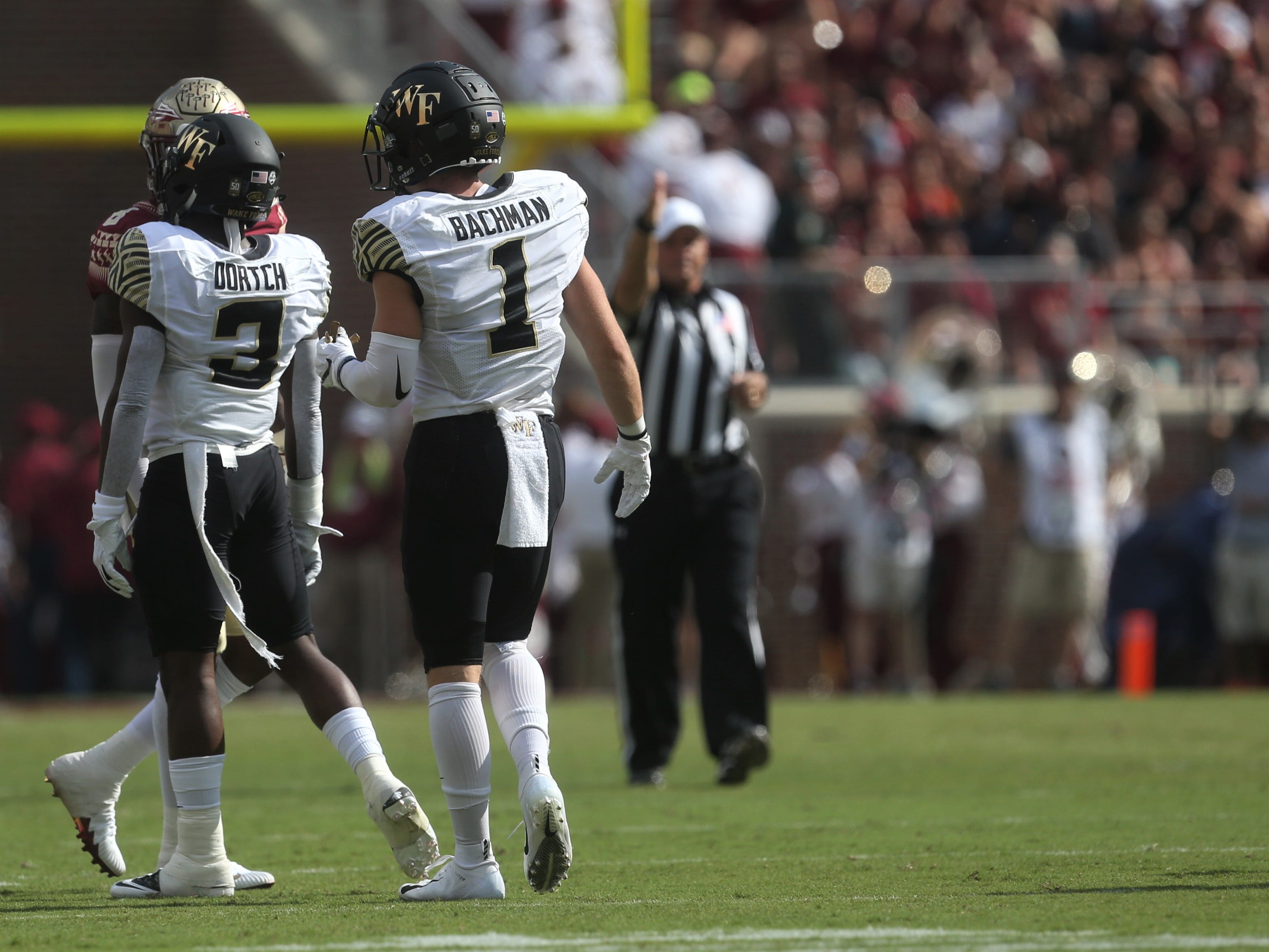 Wake Forest receivers Greg Dortch and Alex Bachman jaw with a Florida State defender during a game at Doak Campbell Stadium on Saturday, Oct. 20, 2018.