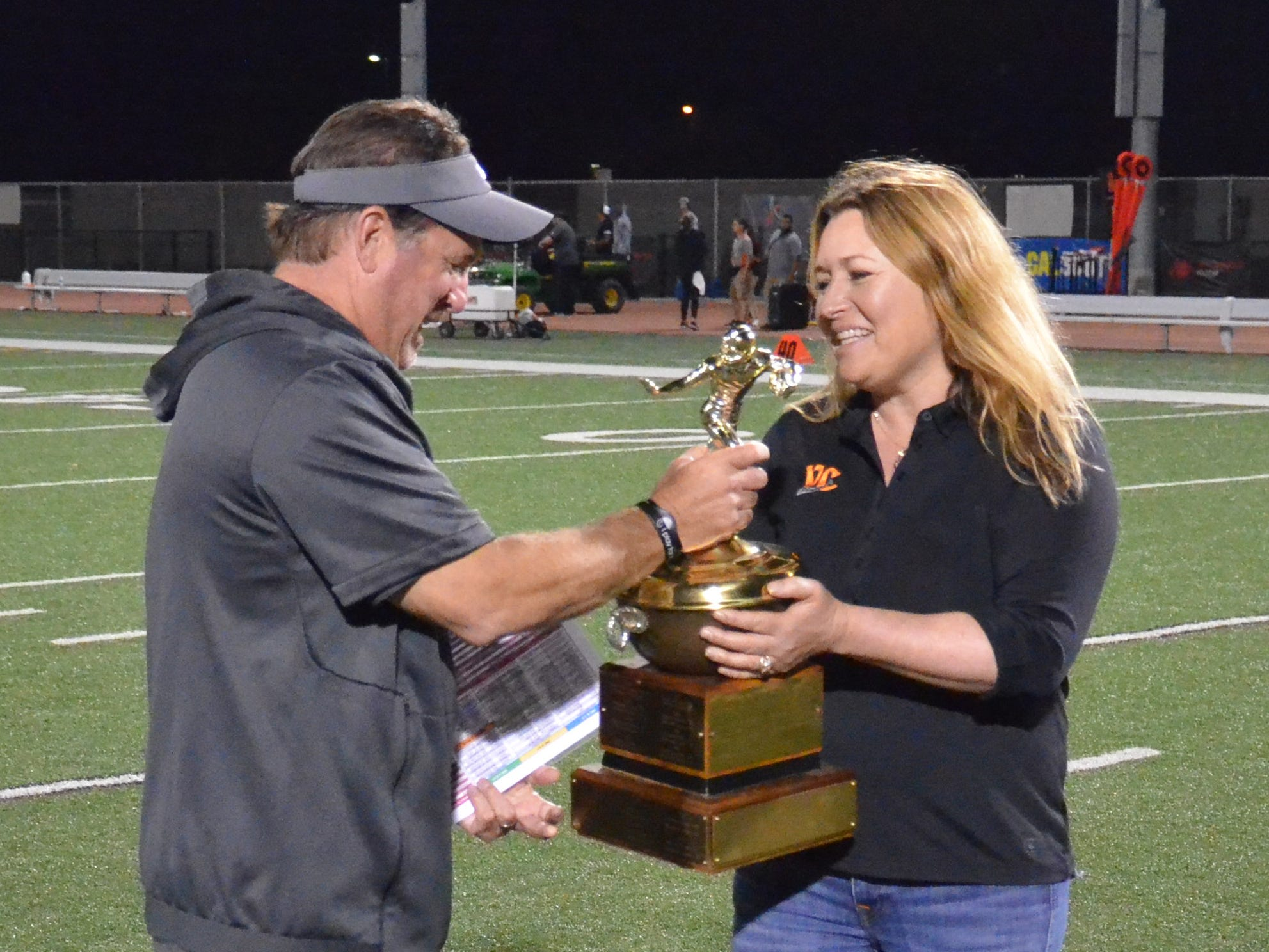 Ventura College interim athletic director Mary Giles (right) hands the Citrus Cup to VC head coach Steve Mooshagian after the Pirates' 62-7 win over rival Moorpark College on Saturday night at the VC Sportsplex.