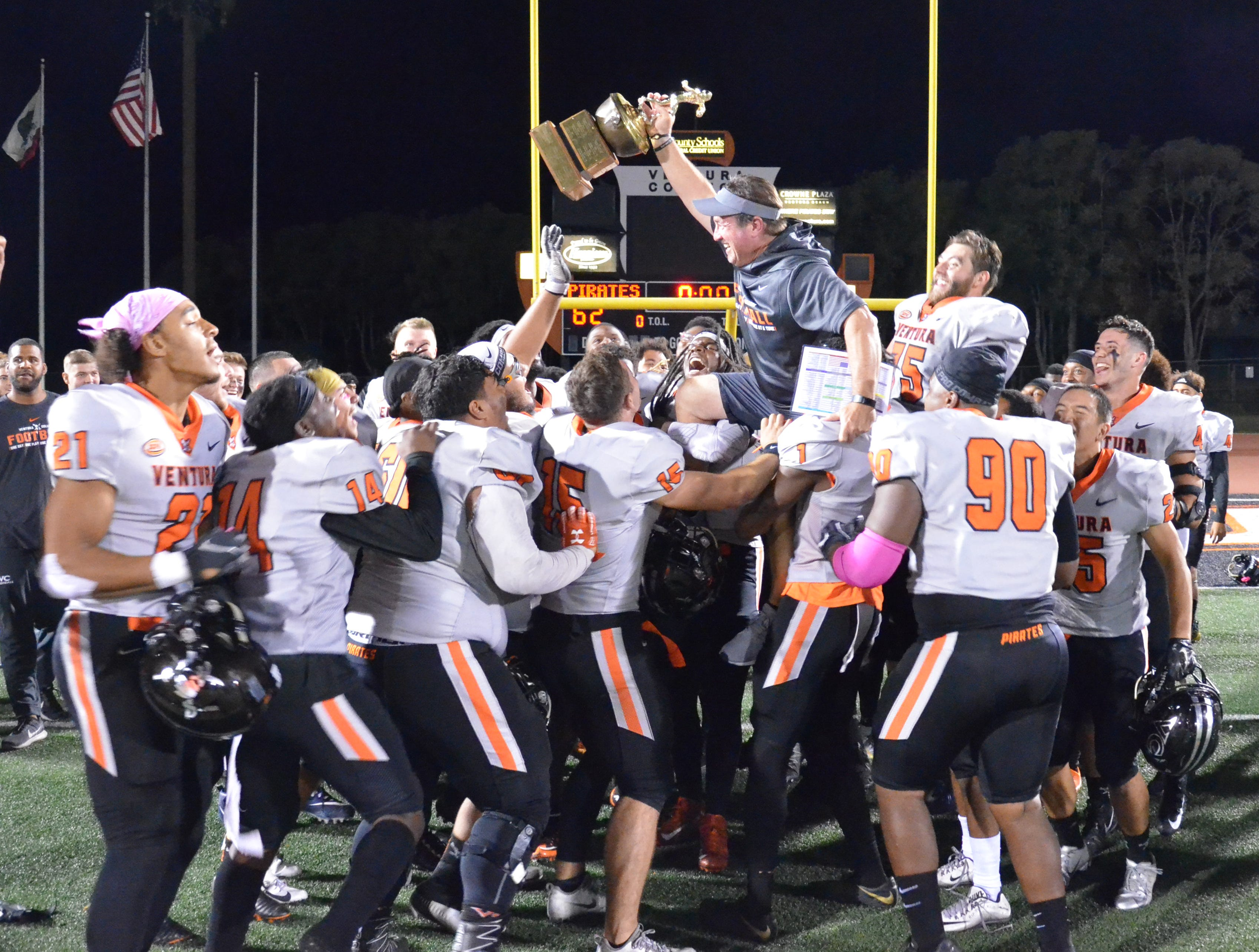 The Ventura College football team carries head coach Steve Mooshagian off the field after the Pirates' 62-7 win over Moorpark College in the 51st Citrus Cup game on Saturday night at the VC Sportsplex.