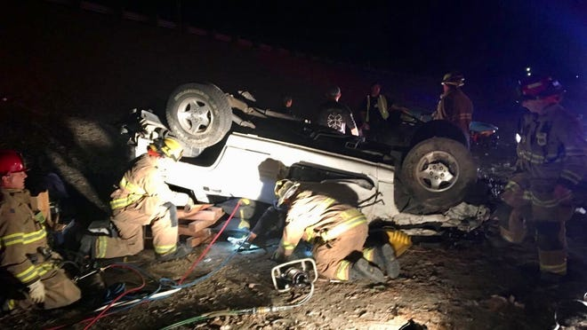 Visalia firefighters work to free a passenger stuck inside a vehicle that overturned near Highway 198 and Plaza drive.