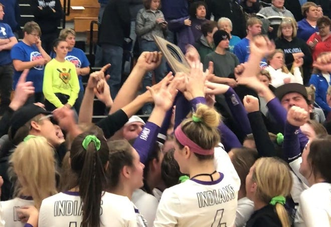 Members of the Mosinee volleyball team hold up a WIAA Division 2 regional title plaque as they are surrounded by members of the school's student section after a win over Merrill on Saturday.