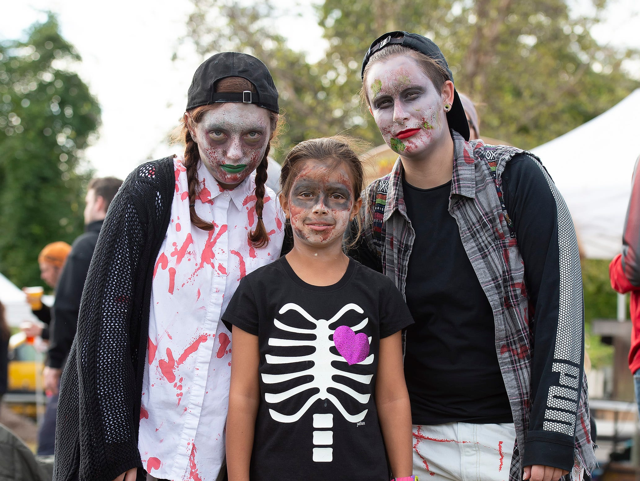Candace Fortney, left, of Dover, Jerny Haines (10) of Milton and AJ Jackson of Dover pose for a photo at Milton Zombie Fest.