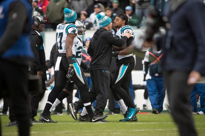 Carolina's Eric Reid is pulled away by his teammates after getting into a dispute during the opening ceremonies in their game against the Eagles Sunday at Lincoln Financial Field.