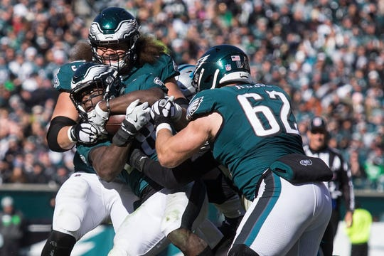 Eagles' Wendell Smallwood is pushed by teammates Isaac Seumalo and Jason Kelce downfield Sunday at Lincoln Financial Field.