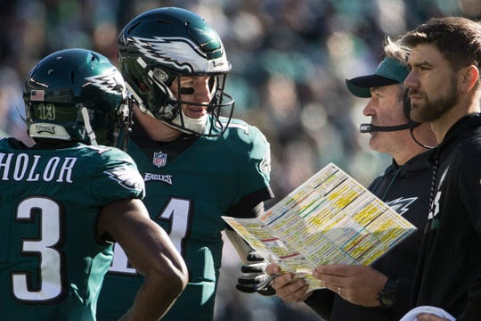 Eagles' Carson Wentz (11) talks with head coach Doug Pederson during a timeout Sunday at Lincoln Financial Field.
