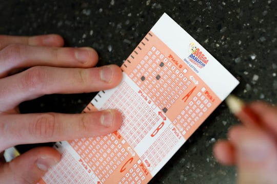 A customer fills out his numbers for a Mega Millions lottery ticket at the Street Corner Market, Wednesday, Oct. 17, 2018, in Cincinnati.