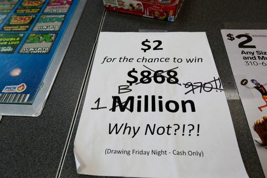 An updated paper sign is displayed the counter of a 7-Eleven store shows that the Mega Millions estimated jackpot has soared to $1 billion, as the second-largest prize in U.S. lottery history gets even bigger, Friday, Oct. 19, 2018, in Chicago.