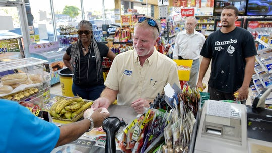 Russell Robinson buys 50 Mega Millions lottery tickets at the Kwik Stop food store at 46th Avenue and Hollywood Boulevard, in Hollywood, Fla., Friday, Oct. 19, 2018.
