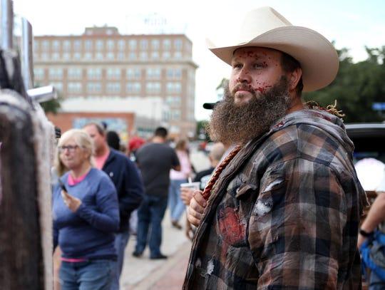 Chad Staelens keeps watch before the start of the Downtown Wichita Falls Development, Inc Zombie Crawl Saturday, Oct. 20, 2018, around downtown Wichita Falls.