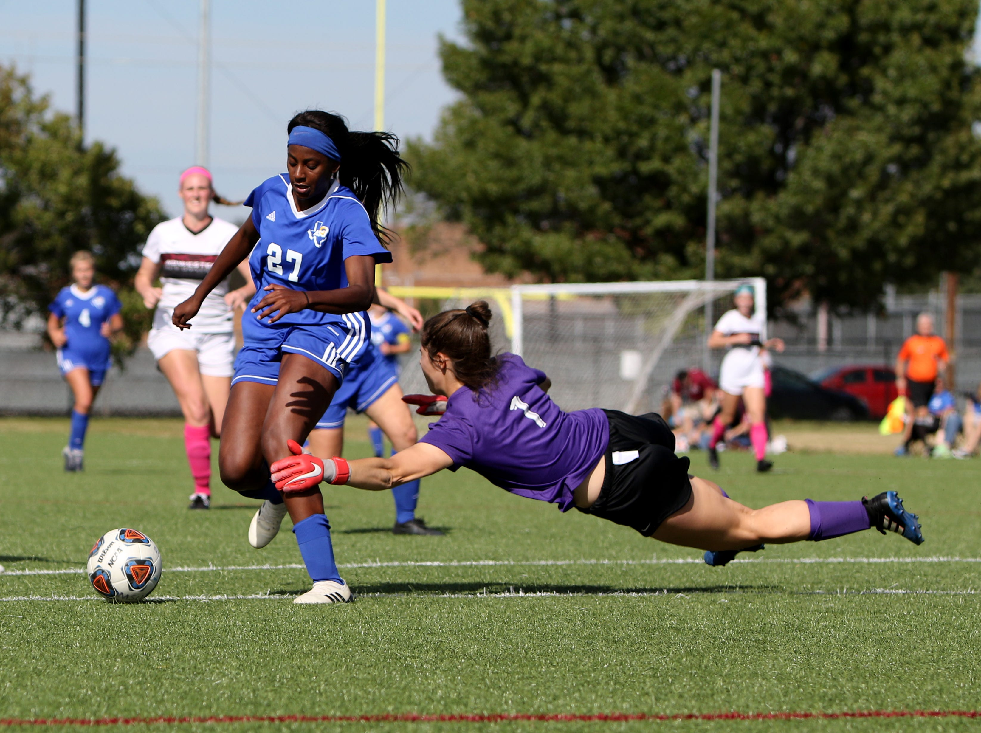 Angelo State's Trenadey Scott beats Midwestern State goalie Samantha Upton to go on to score the winning goal in overtime Sunday, Oct. 21, 2018, on the MSU soccer practice field.