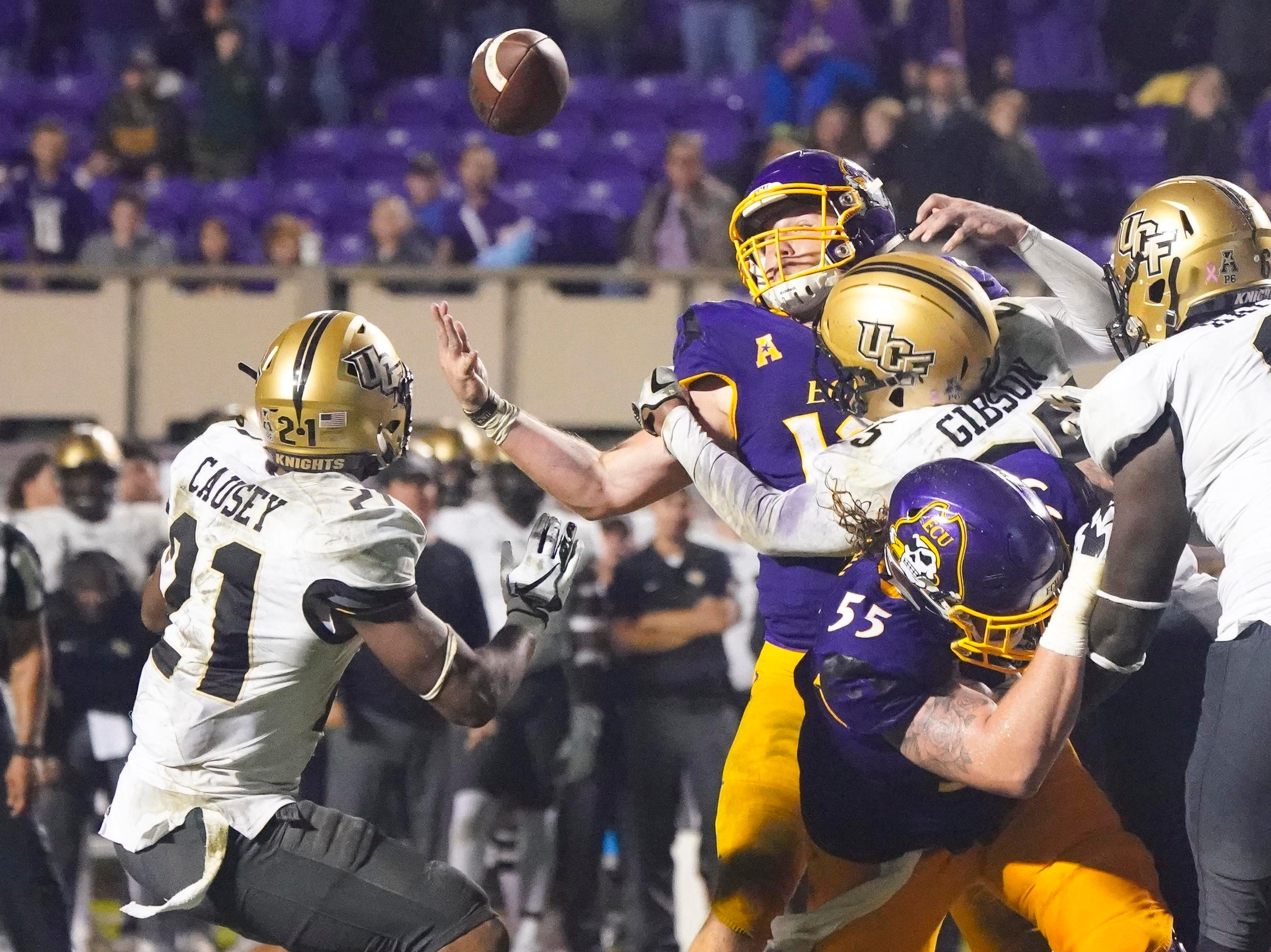 East Carolina Pirates quarterback Holton Ahlers (12) fumbles the ball after being hit by UCF Knights defensive back Kyle Gibson (25) during the forth quarter at Dowdy-Ficklen Stadium.