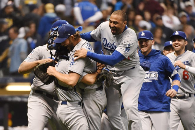 Dodgers pitcher Clayton Kershaw celebrates with teammates after defeating the Brewers in NLCS Game 7.