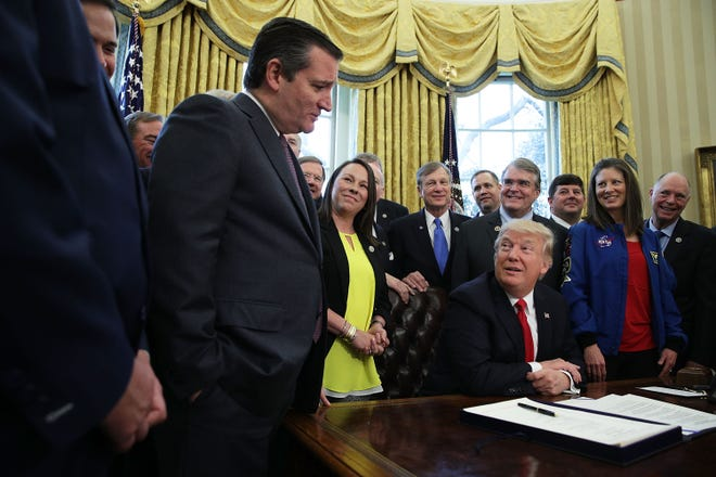 President Donald Trump talks to Sen. Ted Cruz , R-Texas,  during a bill signing ceremony in 2017.