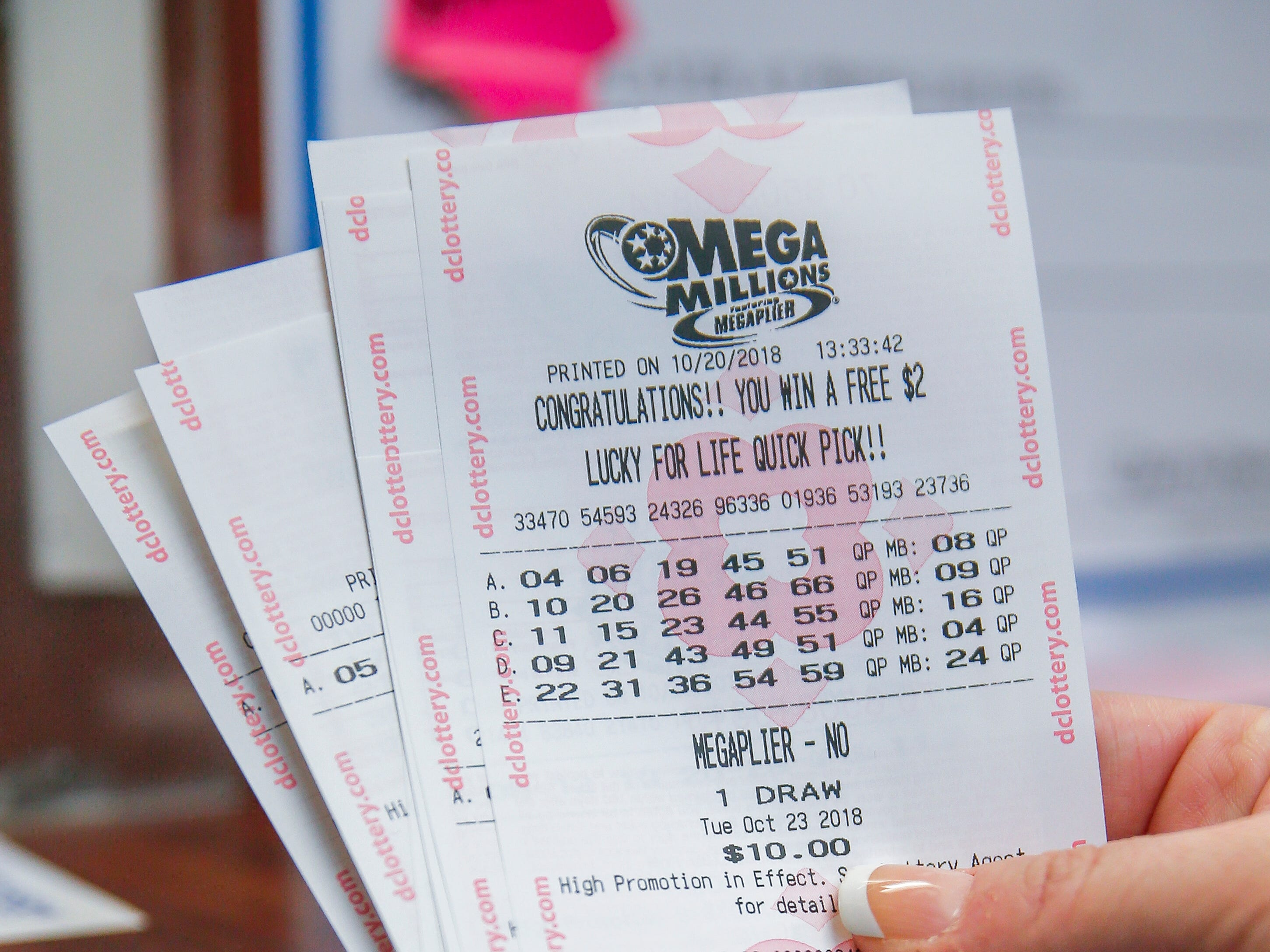 A customer shows her purchased Mega Millions lottery tickets at a retailer in Washington, D.C., Oct. 20, 2018.