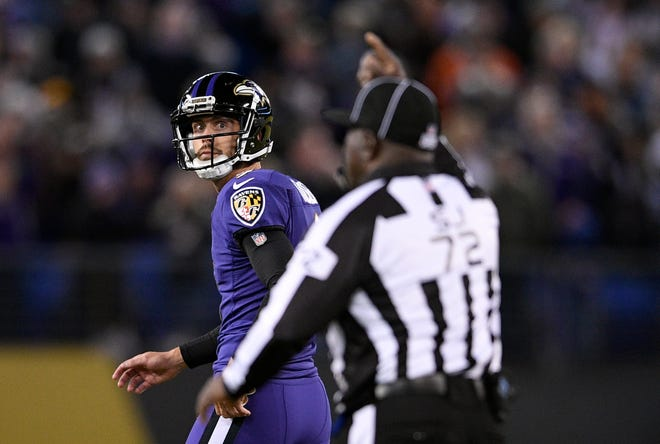 Baltimore Ravens kicker Justin Tucker, left, walks off the field after missing a point after attempt in the second half of an NFL football game against the New Orleans Saints, Sunday, Oct. 21, 2018, in Baltimore.