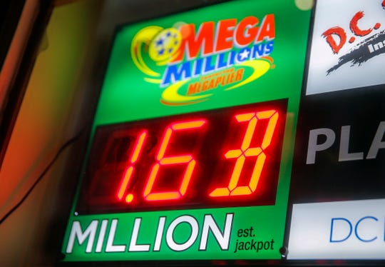A sign displays the estimated Mega Millions lottery jackpot at a retailer in Washington, D.C., Oct. 20, 2018. No winning tickets were sold for the Mega Millions drawing on Friday and the jackpot now grows to 1.6 billion dollars for the next drawing on Tuesday, Oct. 23, 2018.