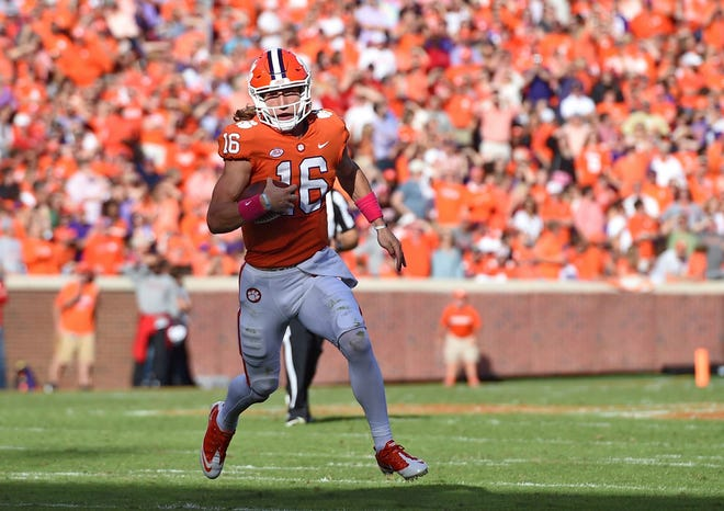 Clemson quarterback Trevor Lawrence scrambles out of the pocket during the first half against North Carolina State.
