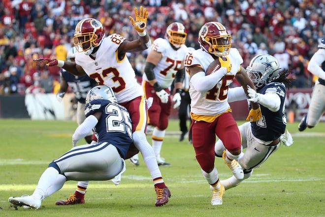Washington Redskins running back Kapri Bibbs (46) carries the ball past Dallas Cowboys linebacker Jaylon Smith (54) to score a touchdown in the first quarter  at FedEx Field.