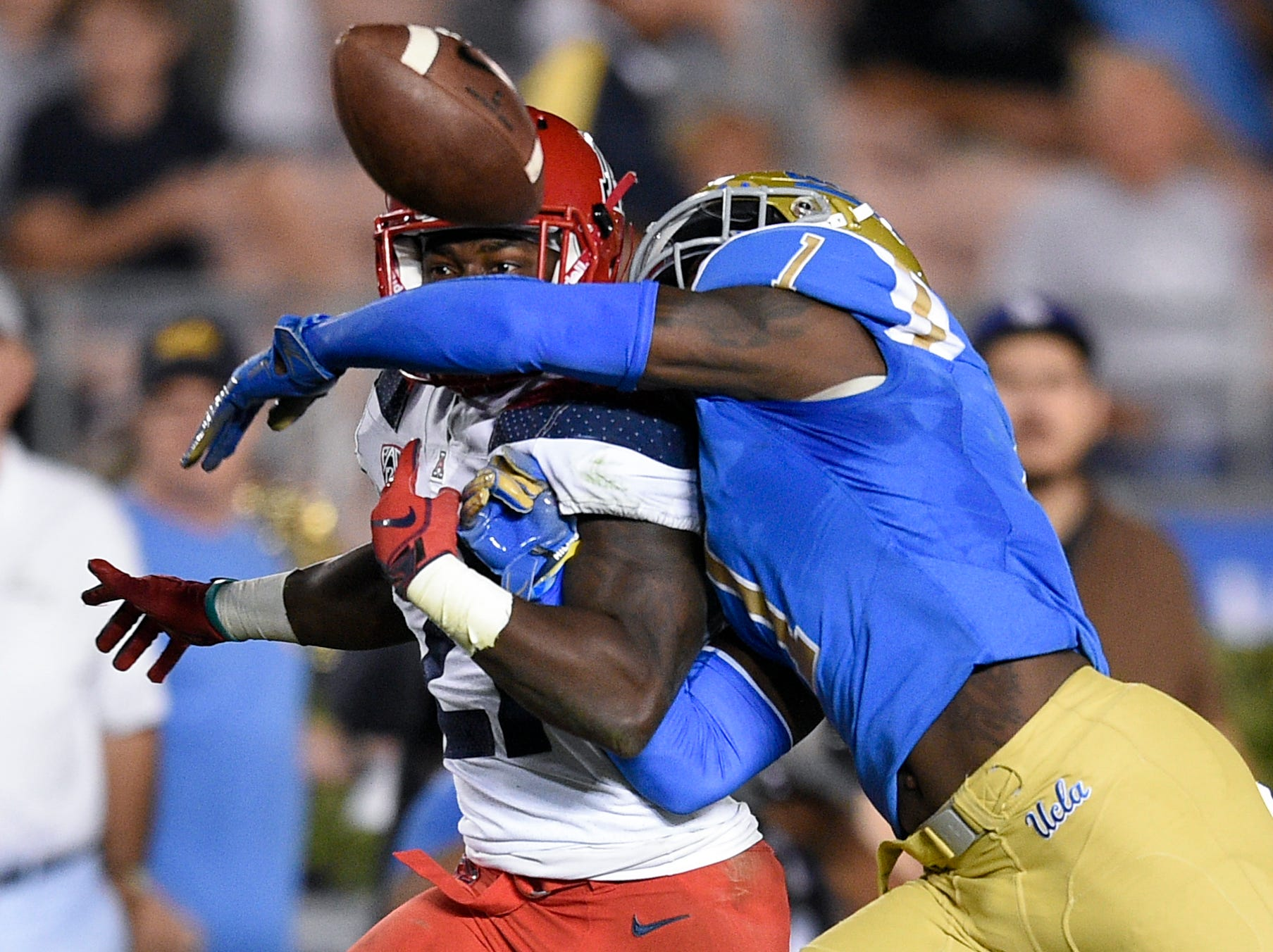 UCLA Bruins defensive back Darnay Holmes (1) knocks the ball away from Arizona Wildcats running back J.J. Taylor (21) for a fumble during the first half at the Rose Bowl.
