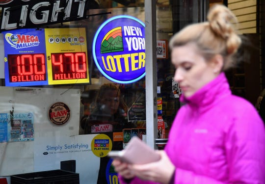 A sign displays the Mega Millions and Power Ball lottery jackpots, Saturday, Oct. 19, 2018 in New York.