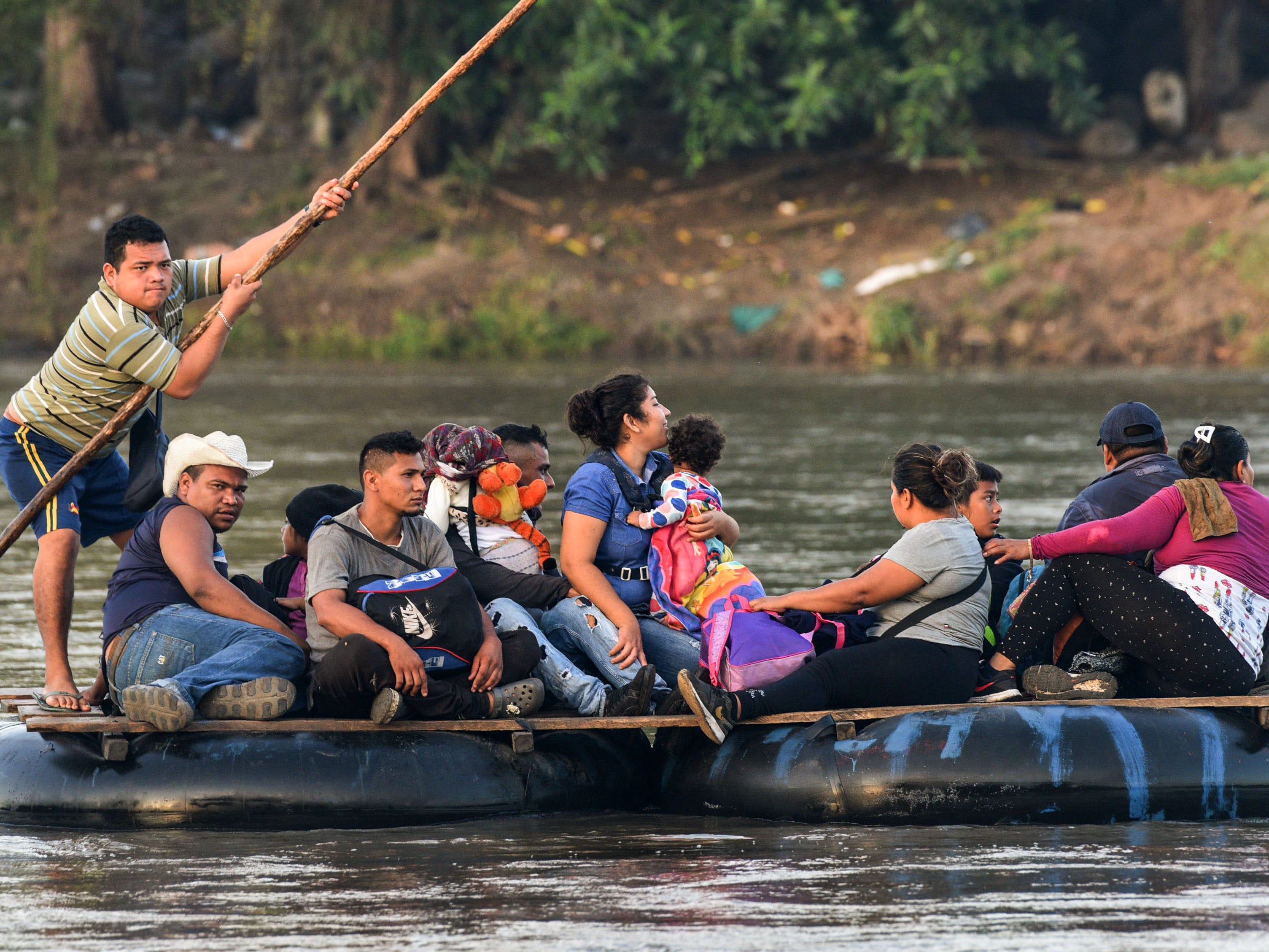 Honduran migrants taking part in a caravan heading to the US, cross the Suchiate River, the natural border between Guatemala and Mexico, in makeshift rafts, in Ciudad Tecun Uman, Guatemala, Oct. 21, 2018.