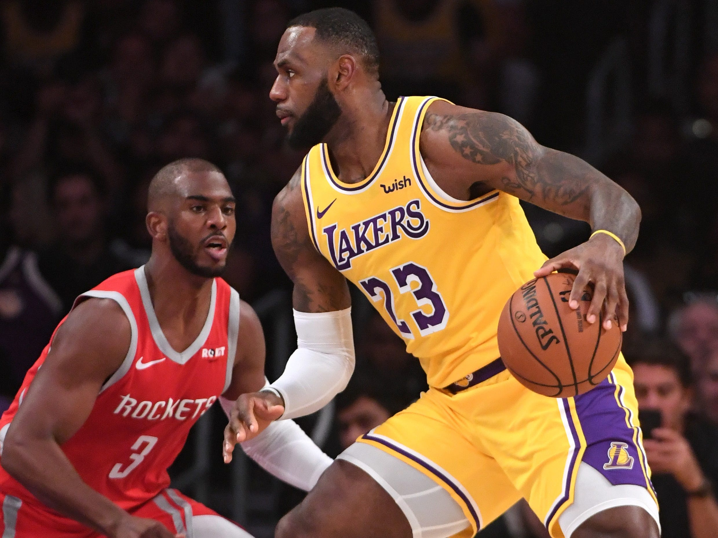 Oct. 20: Lakers forward LeBron James (23) looks for room to work against Rockets defender Chris Paul (3).