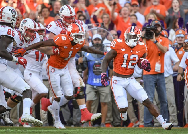 Clemson defensive back K'Von Wallace (12) returns an interception against NC State during the second quarter in Memorial Stadium on Saturday, October 20, 2018.