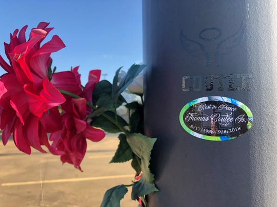 Stickers and flowers decorate a light pole in the Walmart parking lot on Coliseum Boulevard in Alexandria where Thomas Coutee was shot and died. His estranged wife, Kayla Jean Giles, is facing a charge of first-degree murder.