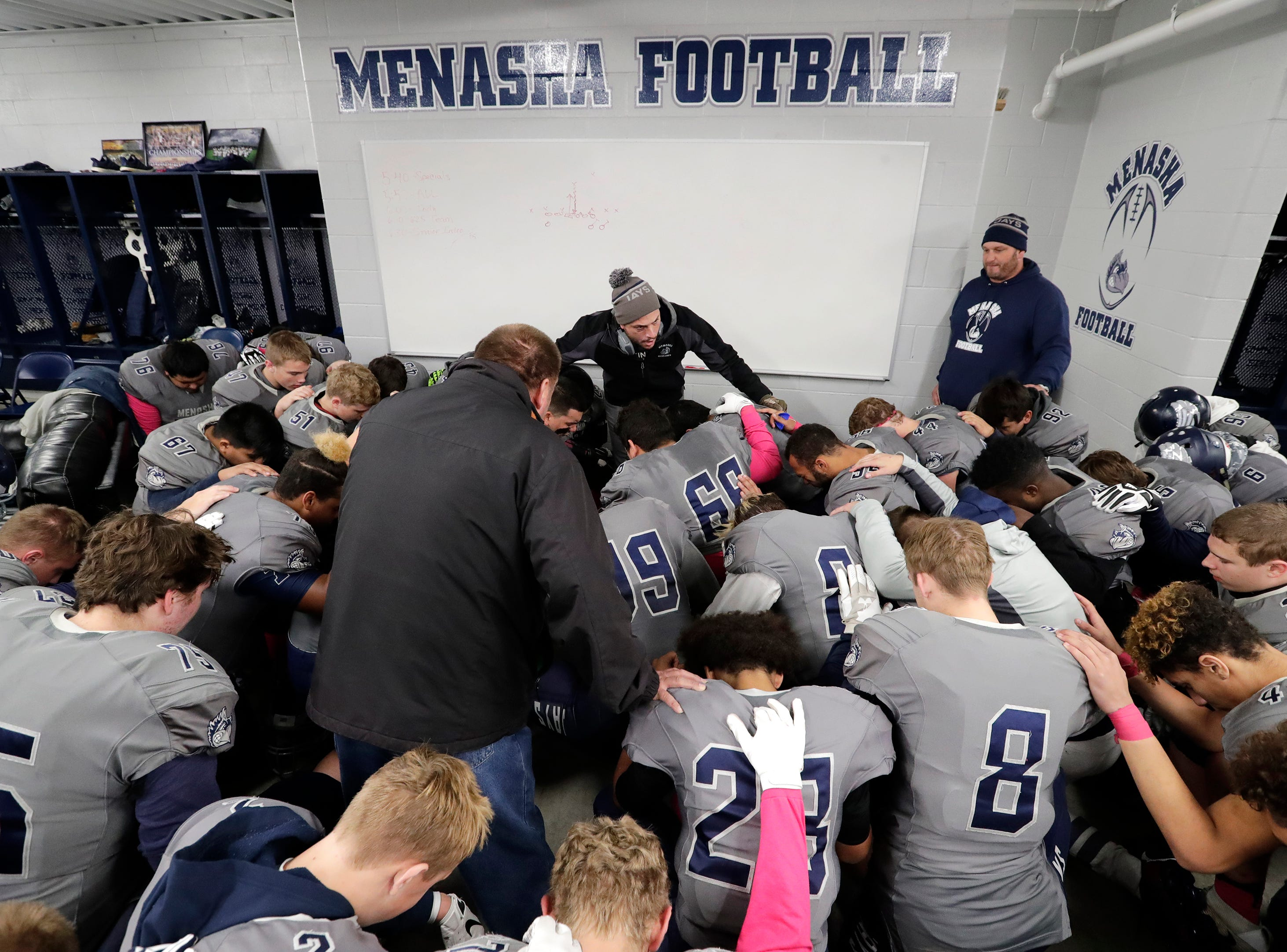 Menasha High School's players and coaches take a moment together before taking to the field against Hortonville High School during their WIAA Division 2 football playoff game Friday, Oct. 19, 2018, at Calder Stadium in Menasha, Wis. 