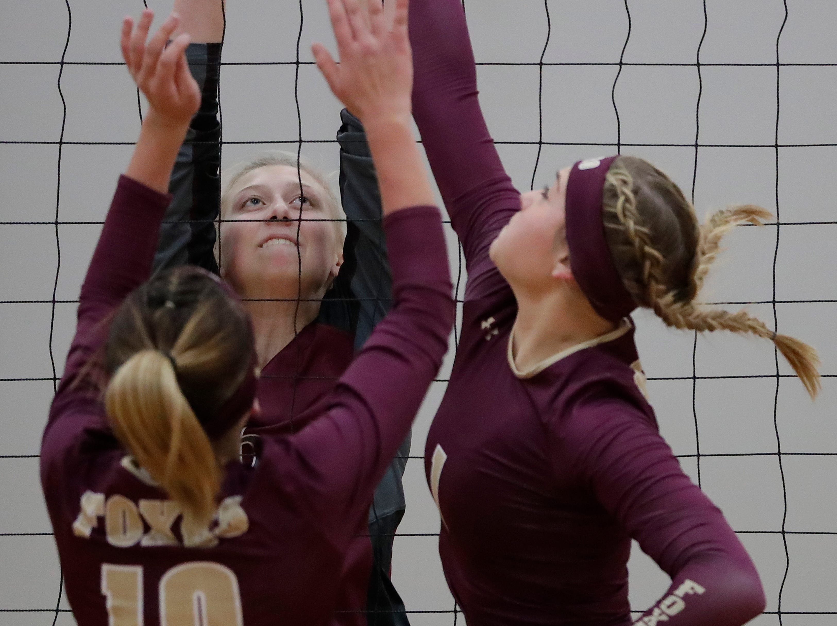 Fox Valley Lutheran High School's Cassandra Patchett (6) defends against Omro High School's Madelyn Larsen (10) and Jadyn Yonke (10) during their girls volleyball match Tuesday, Oct. 16, 2018, in Appleton, Wis. 