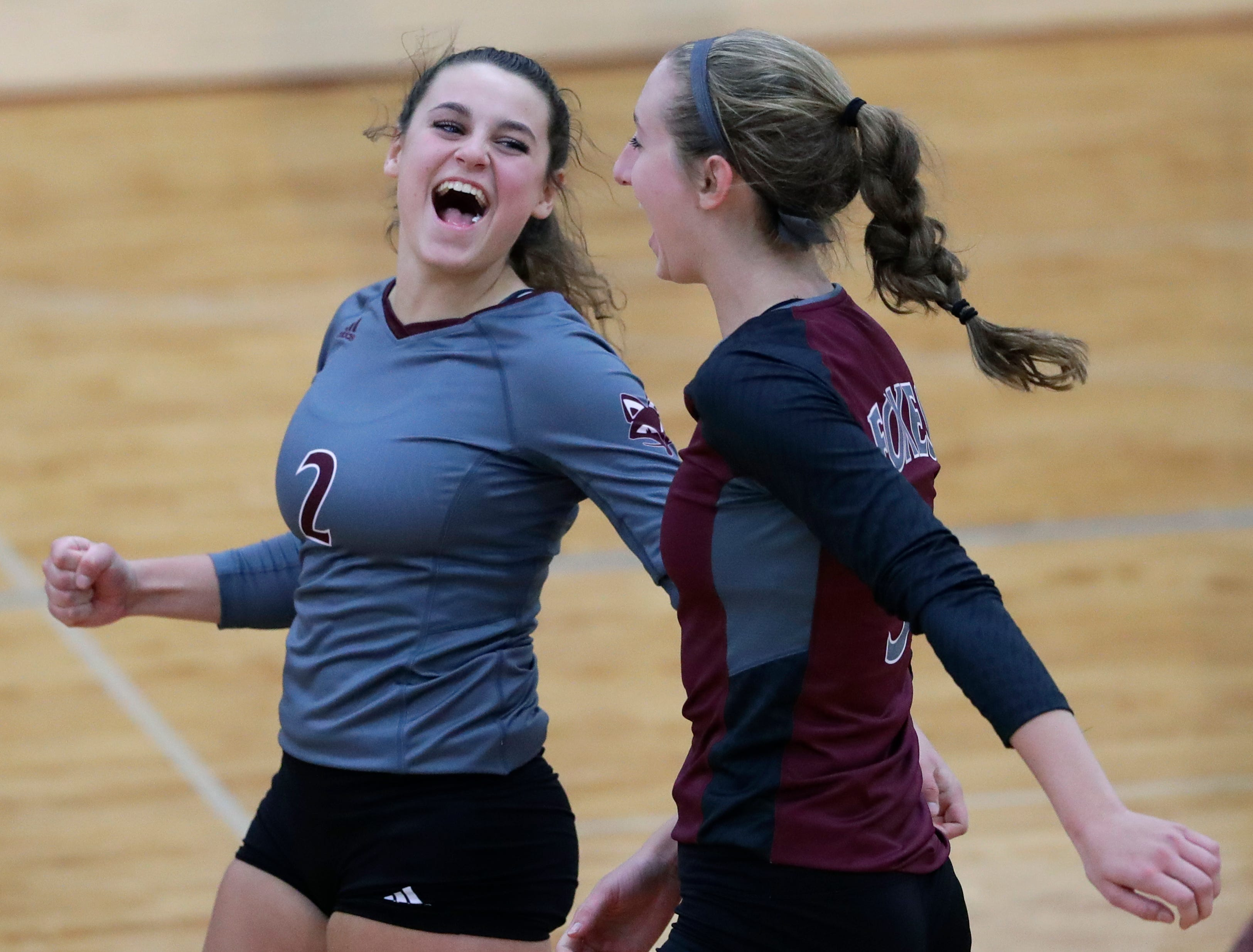 Fox Valley Lutheran High School's Lilly Scheffler (2) and Jenna Charron (3) celebrate winning a point against Omro High School during their girls volleyball match Tuesday, Oct. 16, 2018, in Appleton, Wis. 