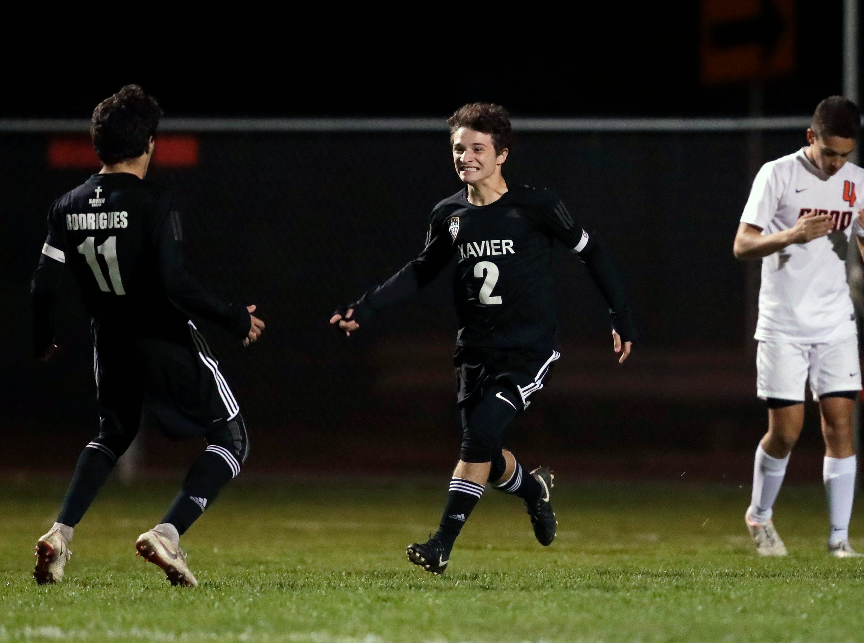 Xavier High School's William Mleziva (2) celebrates scoring a goal with teammate Patrik Rodrigues (11) against Ripon High School's Matt Meincke (4) during their WIAA Division 3 boys soccer regional game Thursday, Oct. 18, 2018, in Appleton, Wis. 