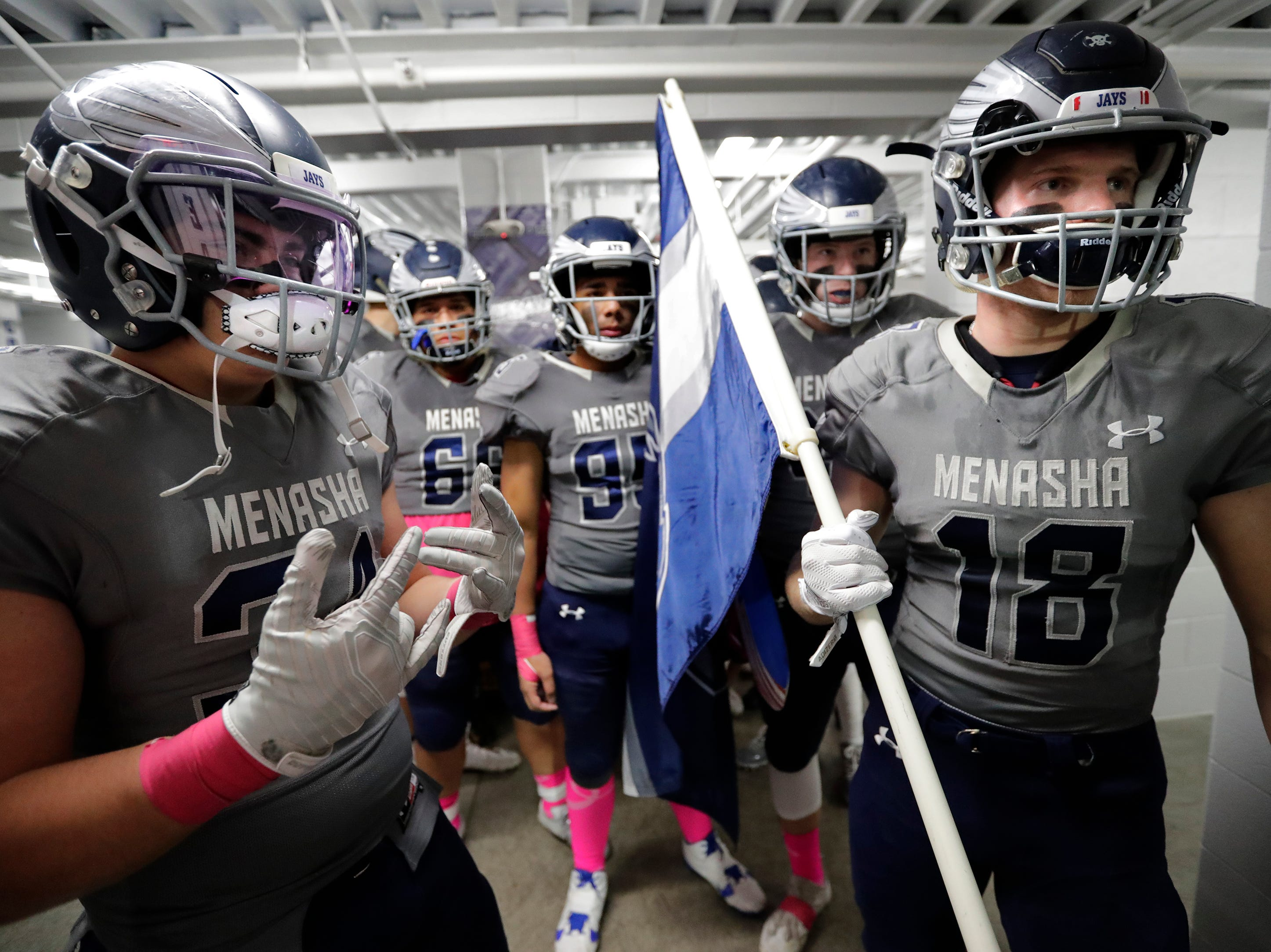 Menasha High School's Reece Racette (34) and Riley Zirpel (18) prepare to lead their team on to the field against Hortonville High School during their WIAA Division 2 football playoff game Friday, Oct. 19, 2018, at Calder Stadium in Menasha, Wis. 