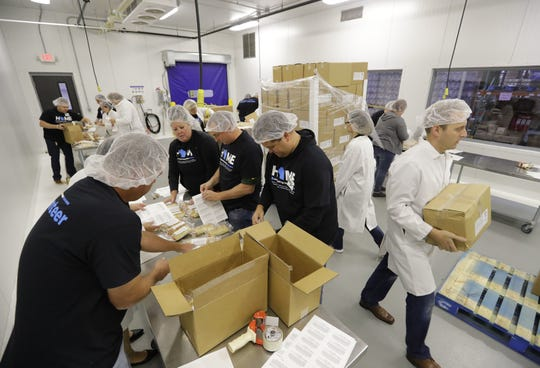 USA TODAY NETWORK-Wisconsin employees conduct quality checks while volunteering during the 2018 Stock the Shelves campaign kick-off event at Feeding America Eastern Wisconsin in Little Chute.