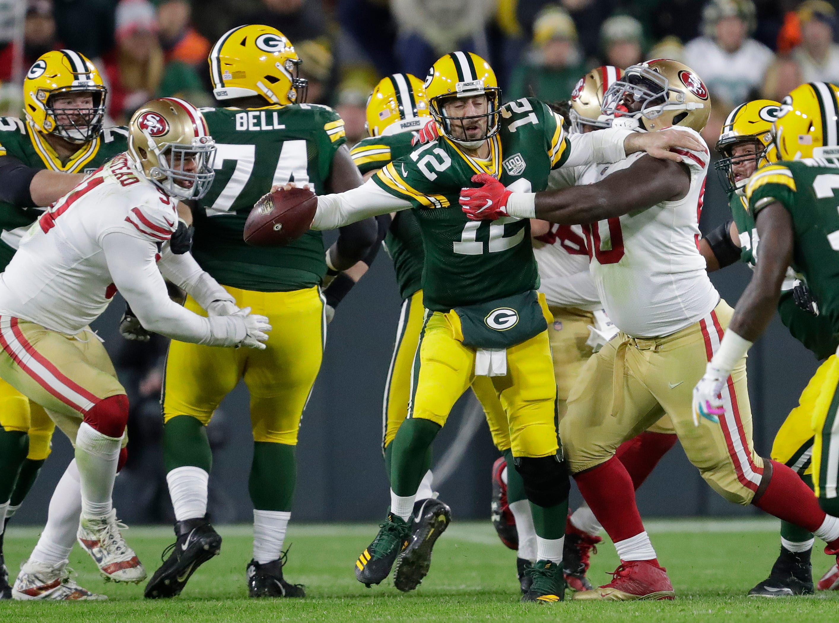 Green Bay Packers quarterback Aaron Rodgers (12) is pressured into throwing an incomplete pass by San Francisco 49ers defensive tackle Earl Mitchell (90) during their football game Monday, Oct. 15, 2018, at Lambeau Field in Green Bay, Wis. 