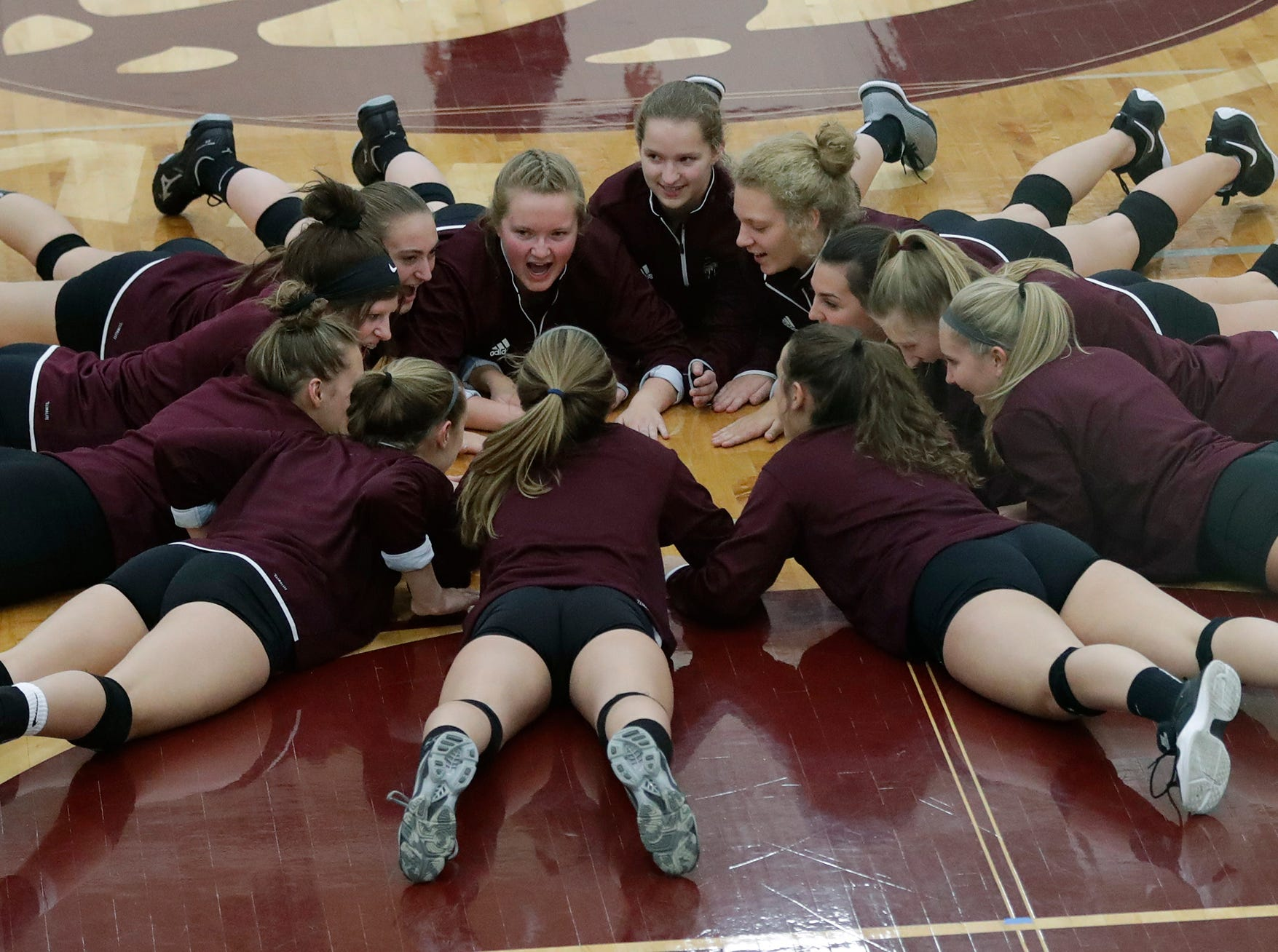 Fox Valley Lutheran High School's players get fired up to play against Omro High School moments before the start of their girls volleyball match Tuesday, Oct. 16, 2018, in Appleton, Wis. 