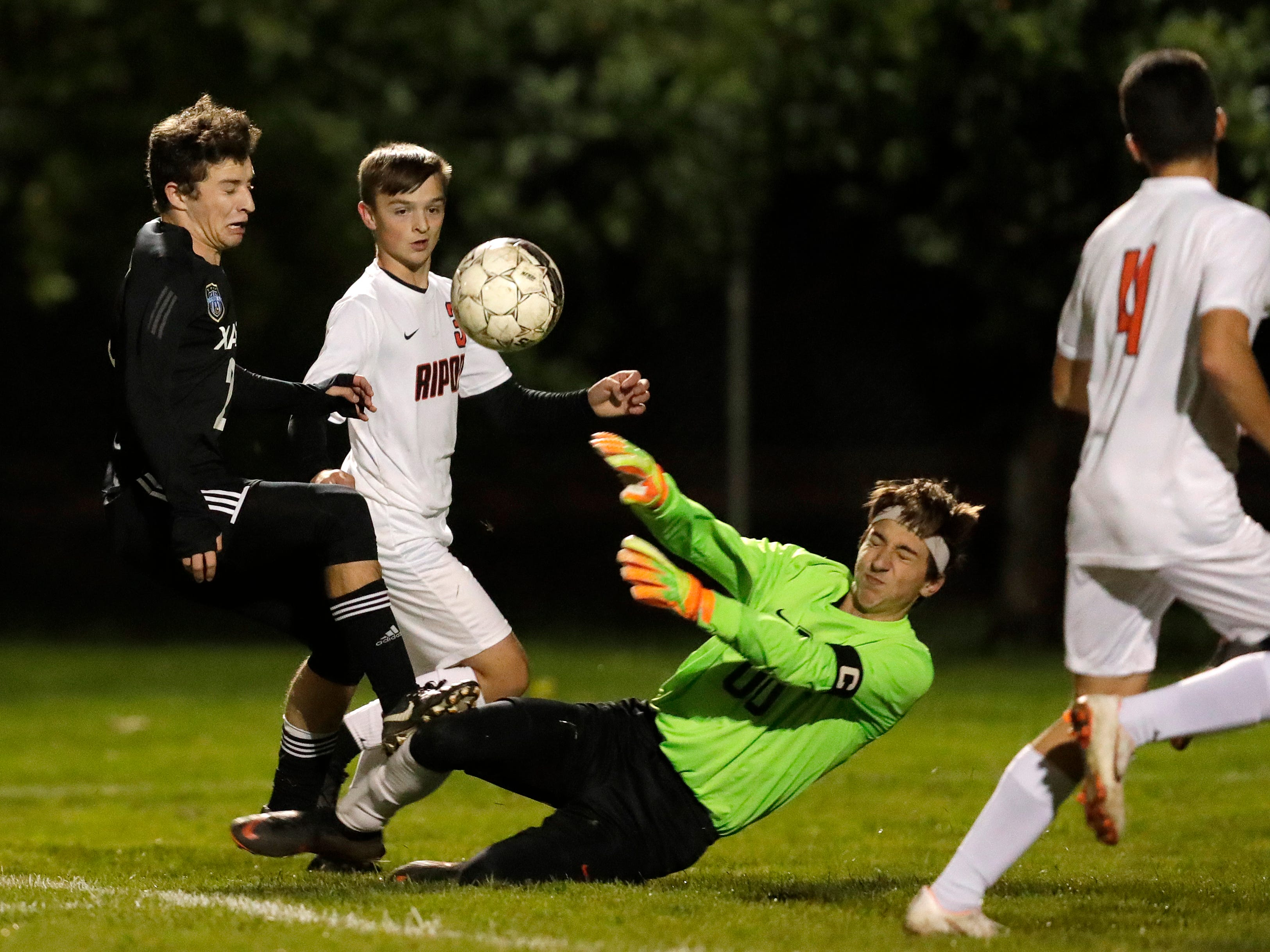 Xavier High School's William Mleziva (2) collides with Ripon High School's goalie Nick Bruesewitz (00) during their WIAA Division 3 boys soccer regional game Thursday, Oct. 18, 2018, in Appleton, Wis. 