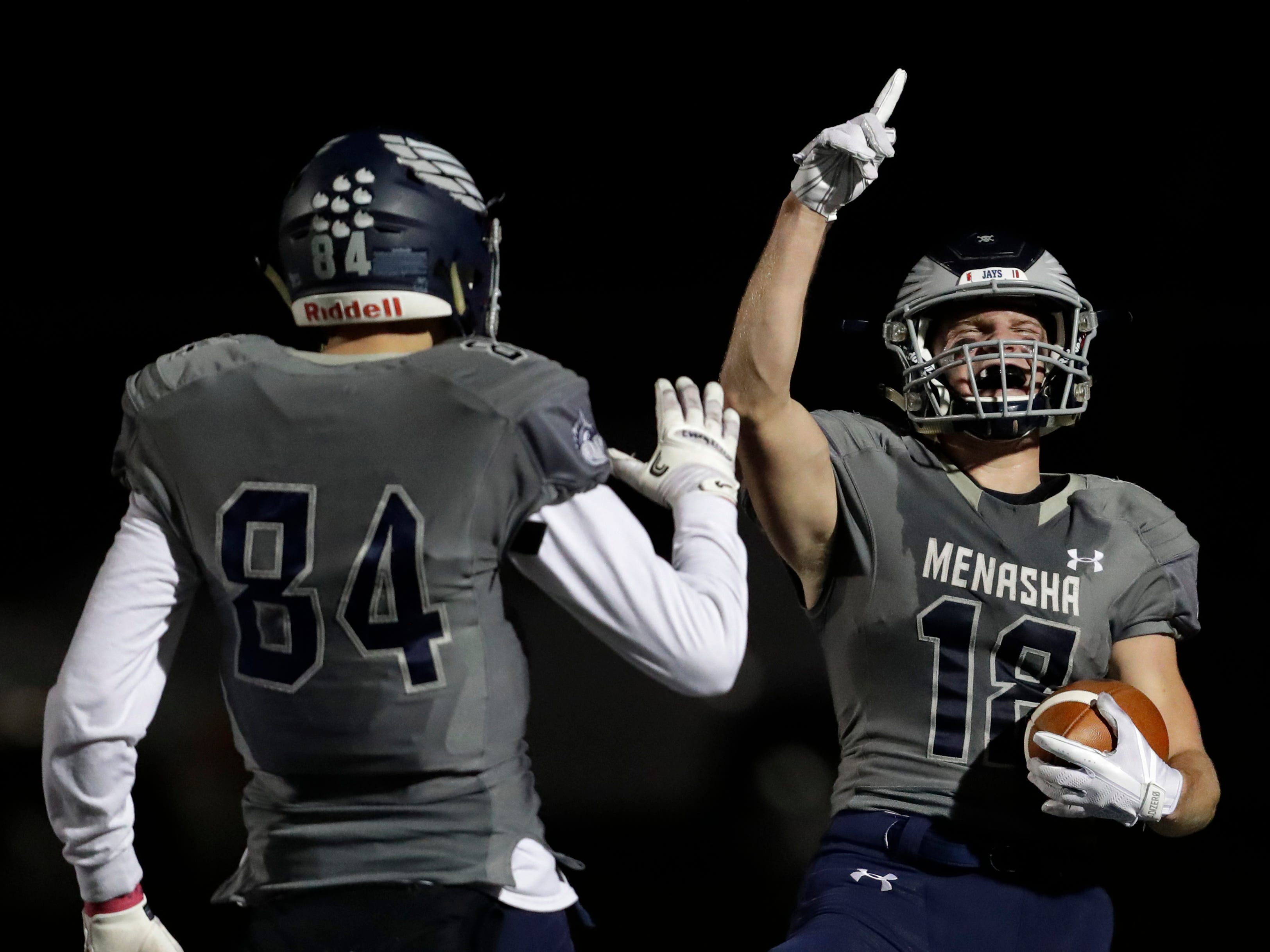 Menasha High School's Riley Zirpel (18) celebrates his 62-yard touchdown reception with teammate Ben Romnek (84) against Hortonville High School during their WIAA Division 2 football playoff game Friday, Oct. 19, 2018, at Calder Stadium in Menasha, Wis. 