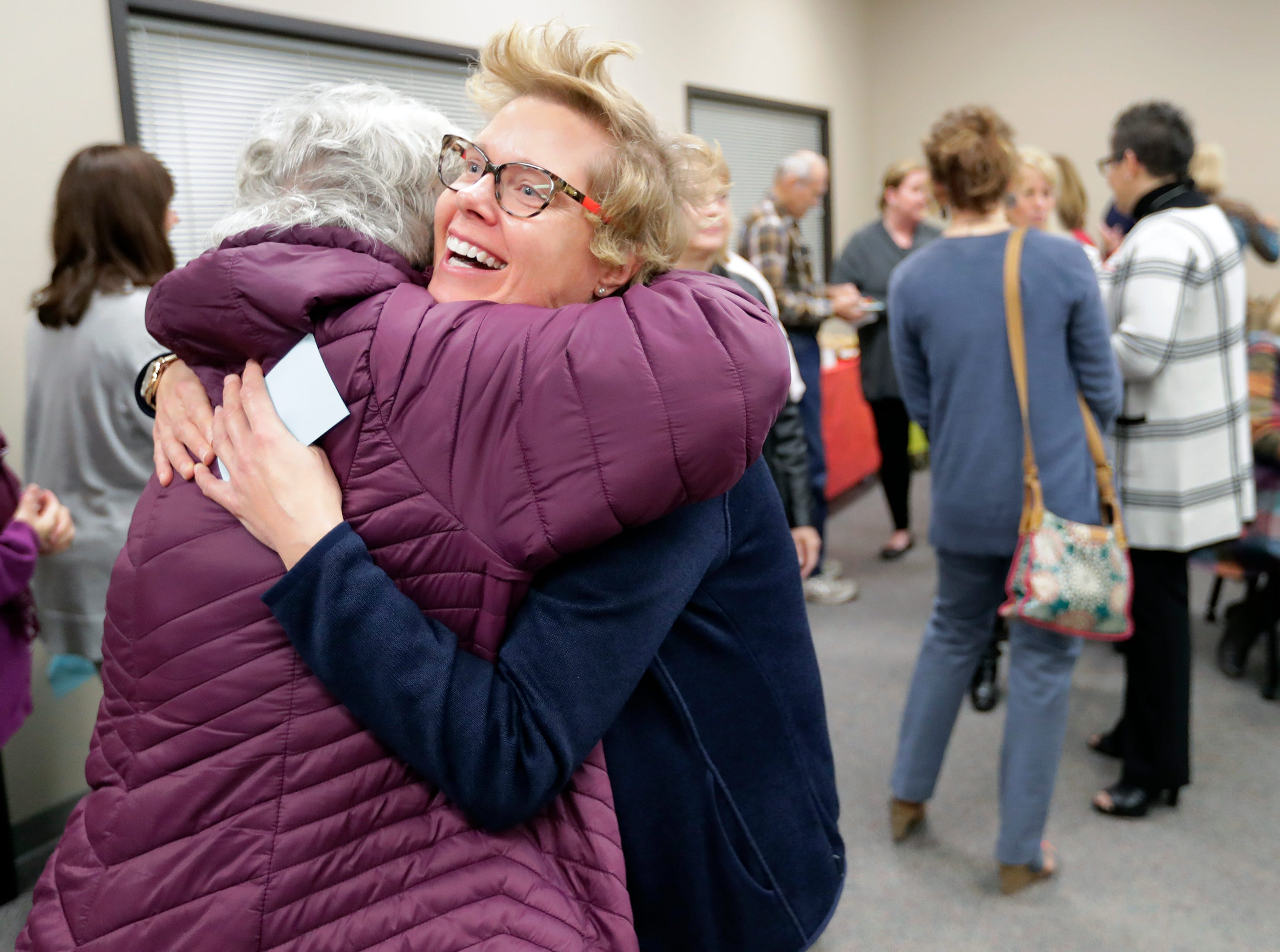 Executive Director Jill H. Grambow, right, gets a hug from her friend and former co-worker Sue Borree during the Fox Valley Memory Project new headquarters open house event Wednesday, Oct. 17, 2018, at Goodwill North Central Wisconsin in Menasha, Wis. 