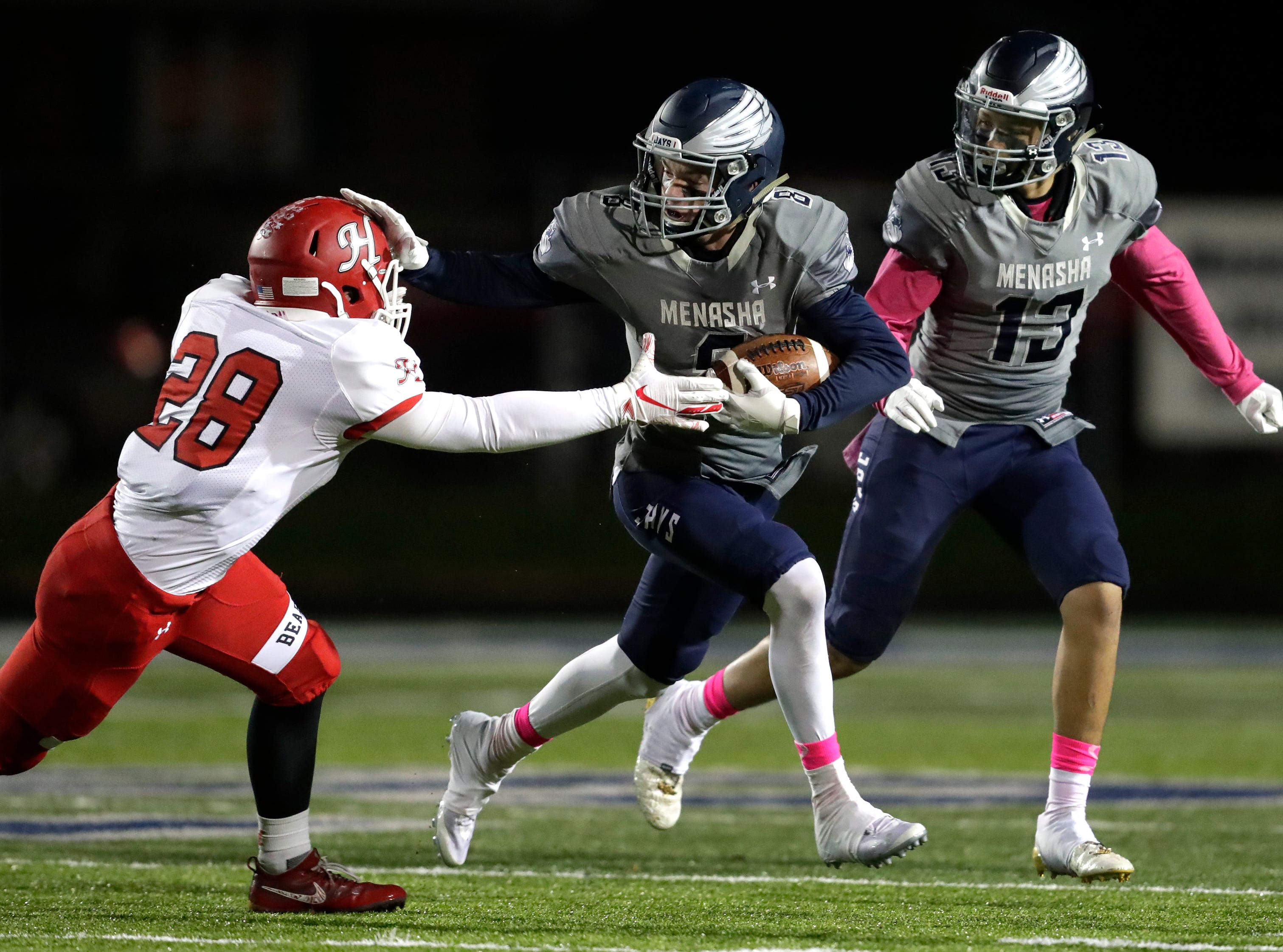 Menasha High School's Brady Jurgella (8) stiff arms Hortonville High School's Gage payne (28) on a punt return during their WIAA Division 2 football playoff game Friday, Oct. 19, 2018, at Calder Stadium in Menasha, Wis. At right is Menasha's Leviathian Fleming (13).