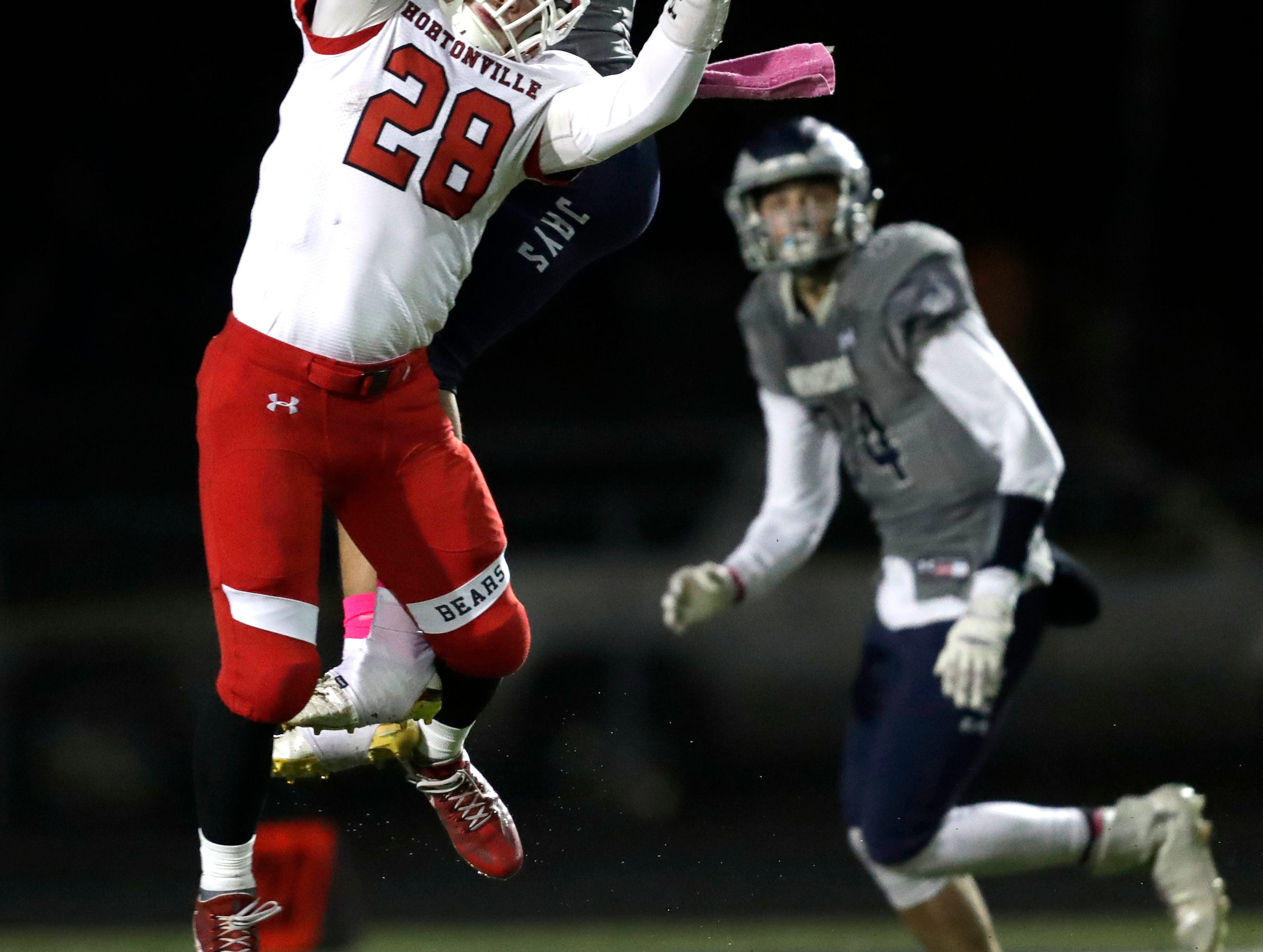 Menasha High School's Leviathian Fleming (13) breaks up a pass intended for Hortonville High School's Gage Payne (28) during their WIAA Division 2 football playoff game Friday, Oct. 19, 2018, at Calder Stadium in Menasha, Wis. 