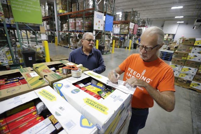 Volunteers Joe Talamanco, left, and Jack Hendriksen, both of Appleton, shrink wrap and organize food for warehouse storage  at Feeding America Eastern Wisconsin during the 2018 Stock the Shelves campaign kick-off event.