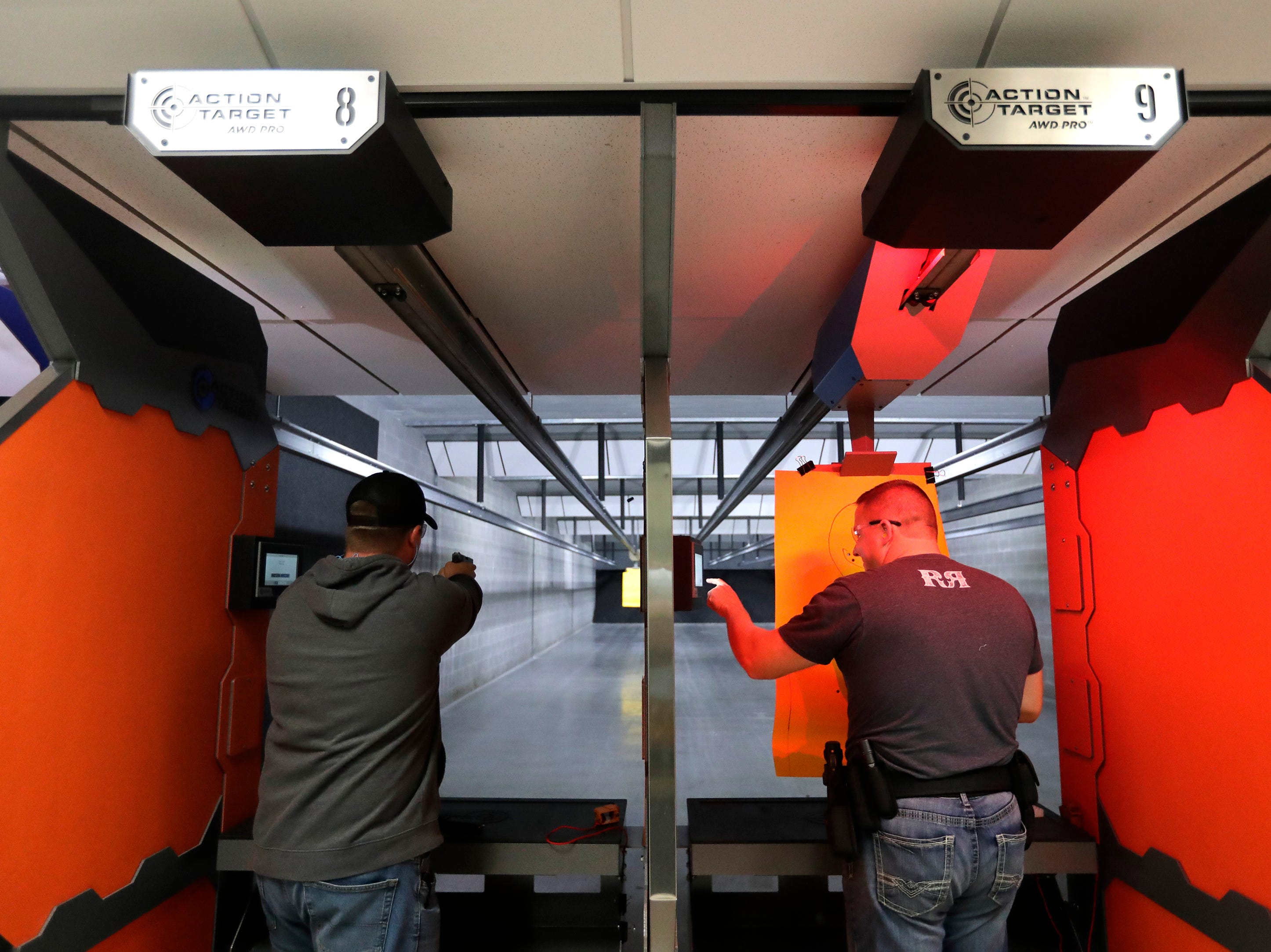 Jake Steinbrink, left, of Hilbert fires his gun as Ben Bastian of Brillion programs his target distance in the shooting range at Trigger Happy Sports Friday, Oct. 12, 2018, in Little Chute, Wis. 