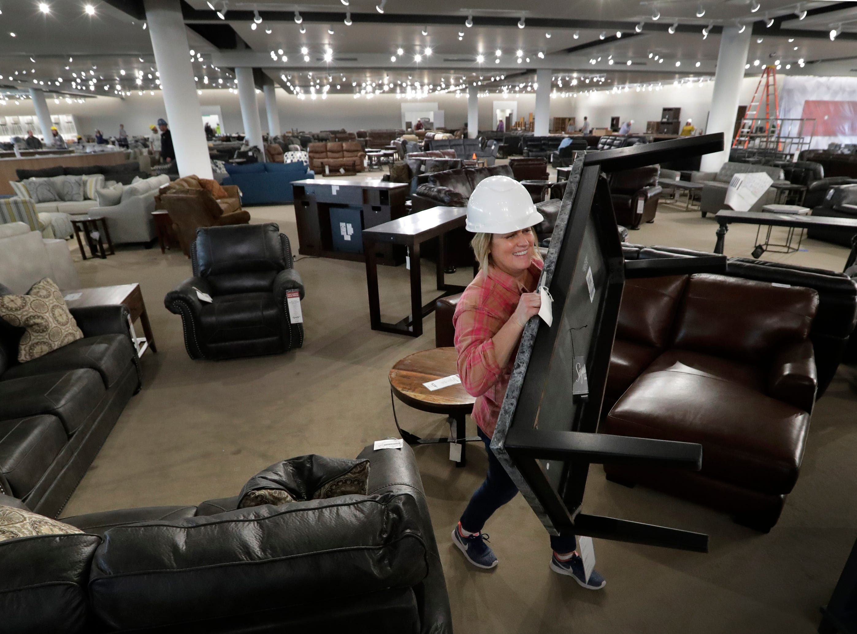 Assistant buyer Jenny Gagan sets up furniture vignettes at the new WG&R store Thursday, Oct. 18, 2018, in Grand Chute, Wis. 