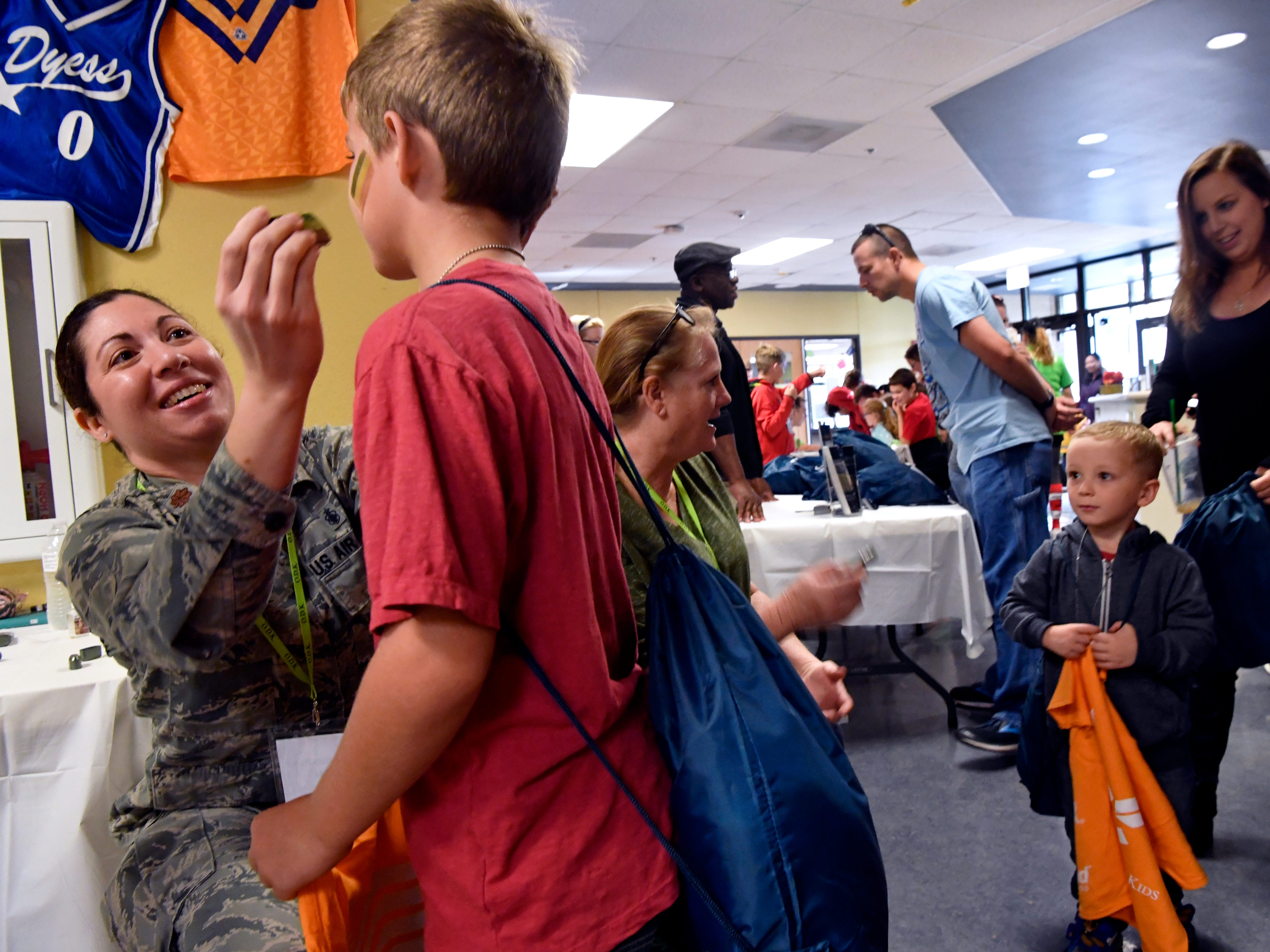 "Jennifer Hessock, a major at Dyess Air Force Base and pediatric nurse practitioner, ""immunizes"" Landon Hansen, 9, with face paint during Operation Dyess Kids Saturday Oct. 20, 2018. The program educates military children on the steps their parents take when mobilizing for deployment by recreating the process in a kid-friendly atmosphere."