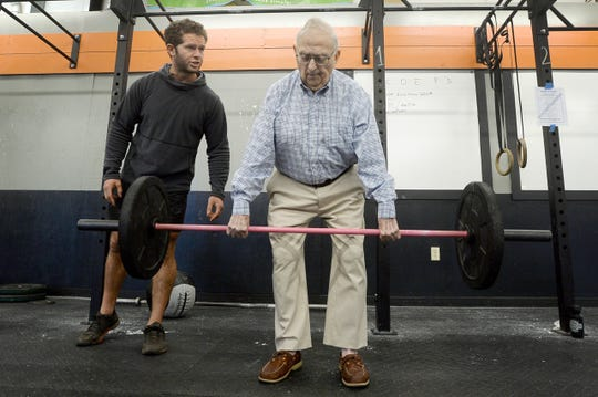 Ned Gibson, 92, is encouraged by coach Marc Mazza as he does a dead lift in the Fit to Fight Alzheimer's challenge at Crossfit Asheville October, 20, 2018. The team challenge raised $2,000 for WNC Alzheimer's Association.