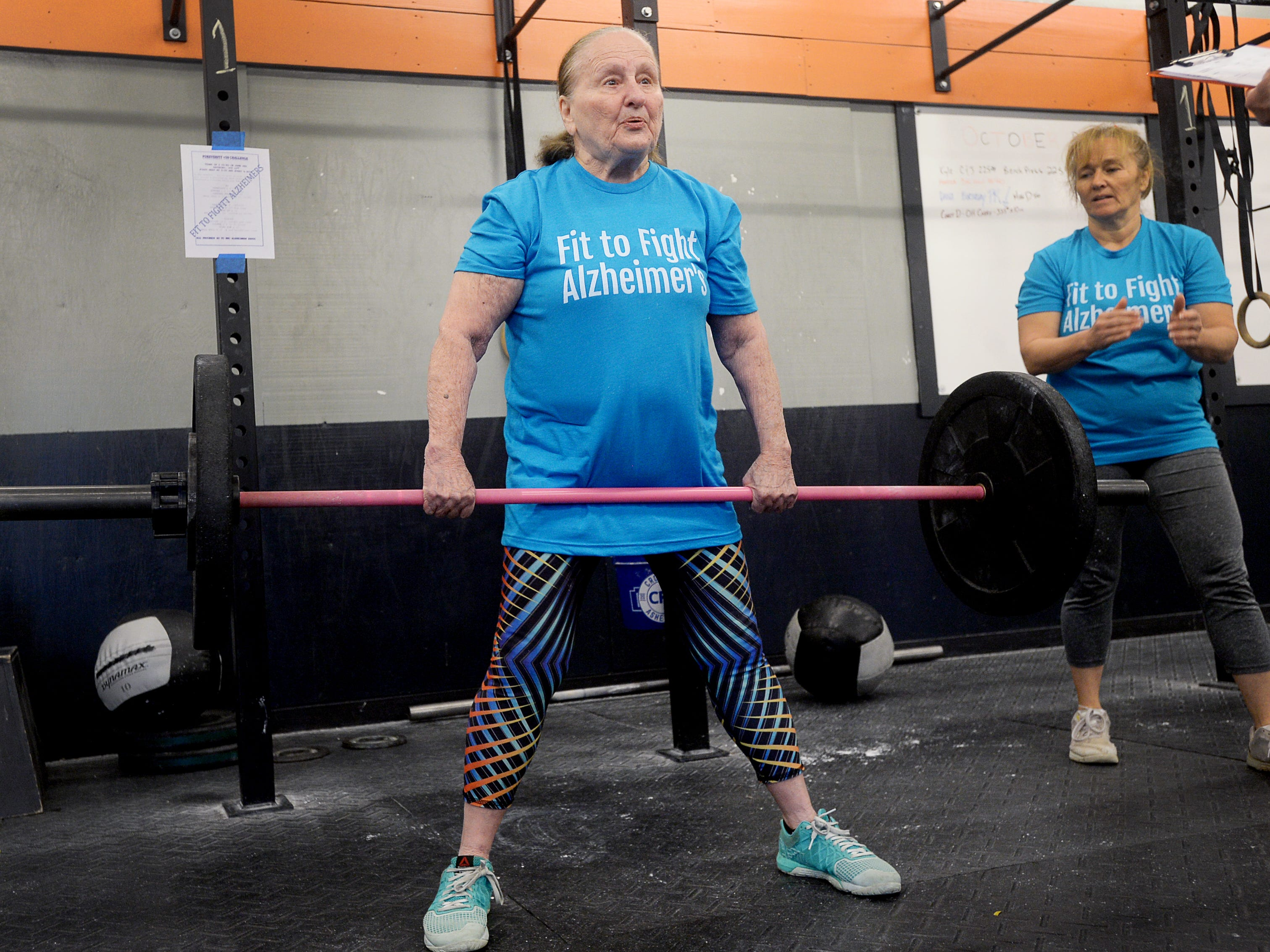Elaine Fox, 83, does a dead lift as her teammate and daughter, Holly Hollifield, encourages her in the Fit to Fight Alzheimer's challenge at Crossfit Asheville October, 20, 2018. The challenge was open to people 50 and up and raised $2,000 for WNC Alzheimer's Association.